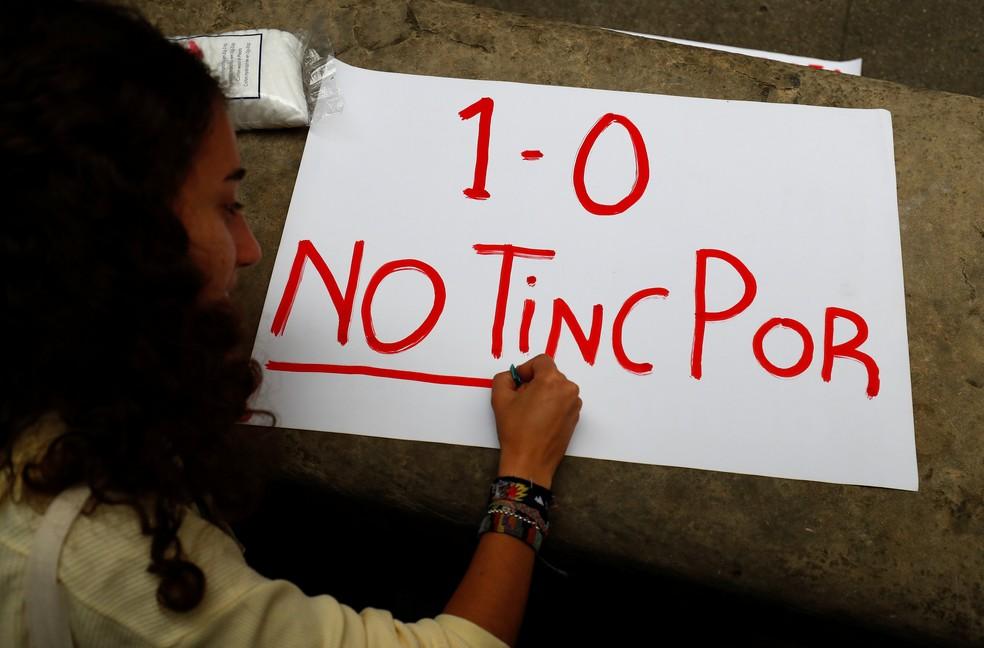 Menina escreve cartaz sobre referendo independentista: