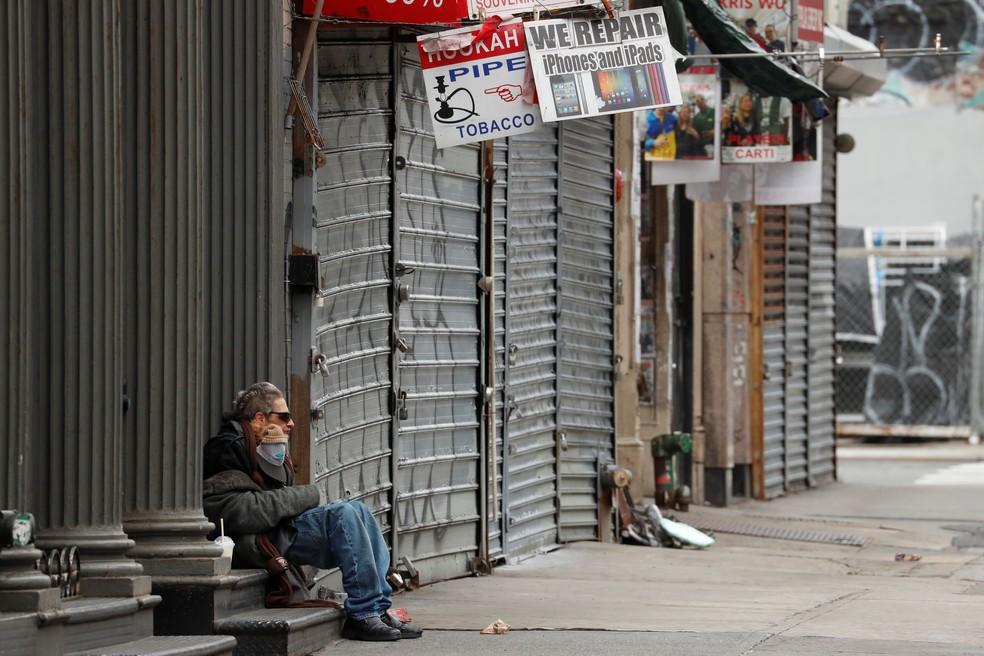 Homem sentando em frente a comércio fechado por causa da Covid-19 em Nova York, em 27 de abril de 2020 — Foto: Lucas Jackson/Reuters