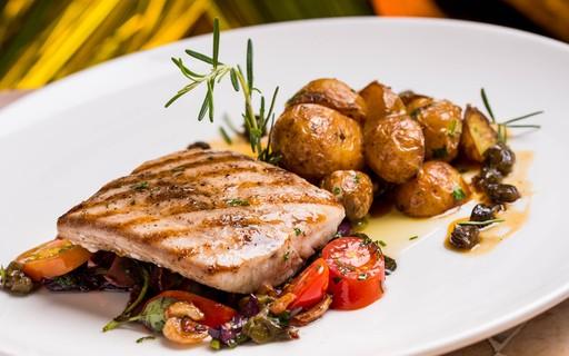 Peixe grelhado com batatas e cama de vegetais