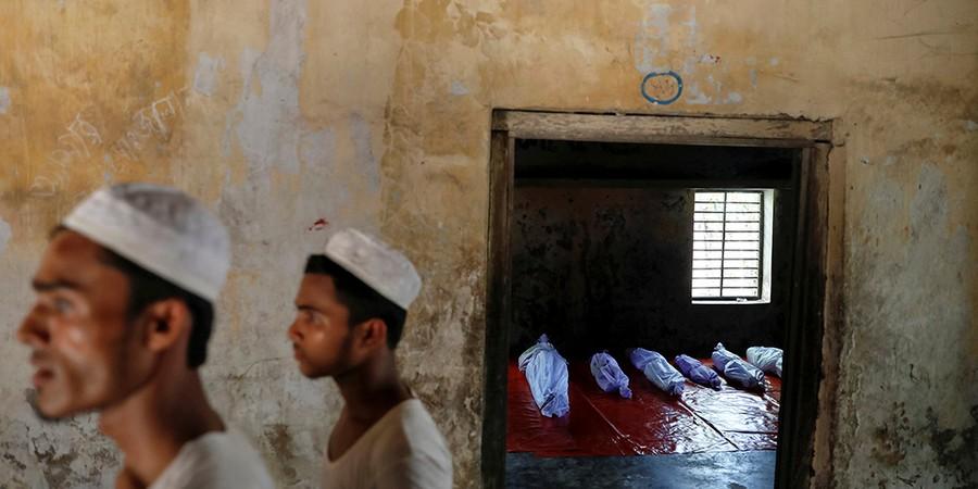 Cena de uma escola islâmica em Bangladesh, onde jazem corpos de refugiados mortos quando o barco em que fugiam virou (Foto: FOTÓGRAFOS/REUTERS)
