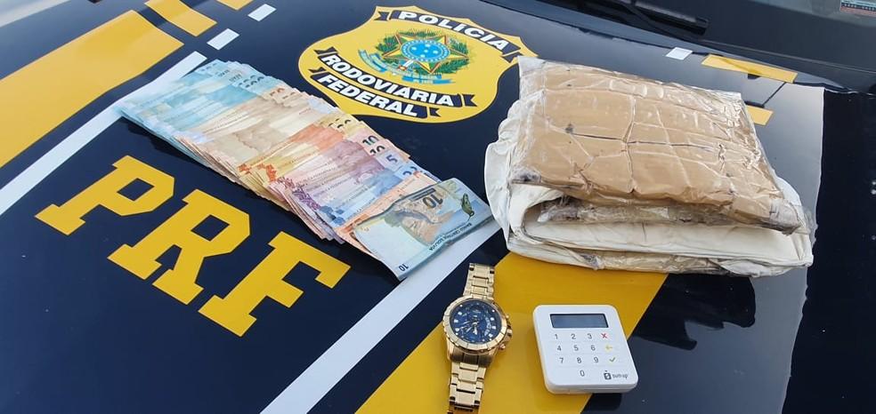 """""""Cinta"""" de pasta base de cocaína, quase R$ 8 mil em dinheiro, relógio e máquina de cartão foram apreendidos — Foto: PRF/Divulgação"""