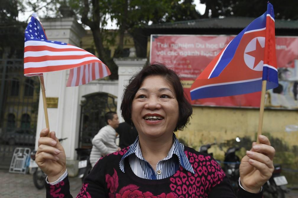 Mulher vai às ruas com as bandeiras dos EUA e da Coreia do Norte acompanhar comboio com o líder norte-coreano Kim Jong-un — Foto: Susan Walsh/AP Photo