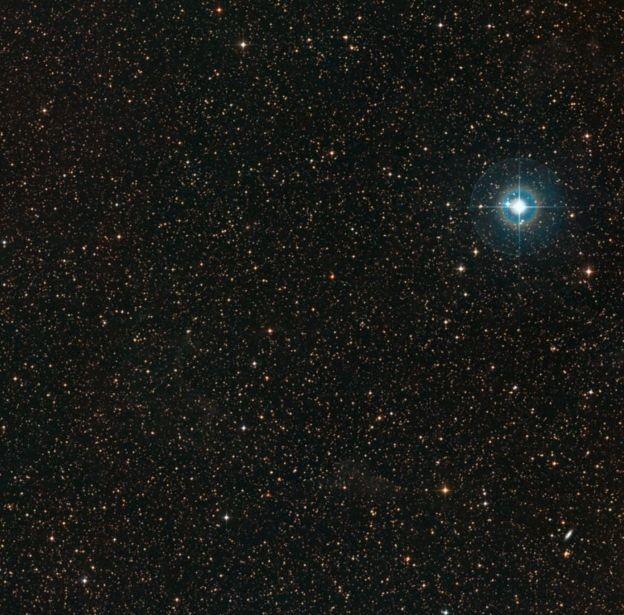 A PDS-70 é o ponto laranja pálido no meio da imagem. A estrela azul brilhante no canto é a Chi Centauri (Foto: ESO/DIGITIZED SKY SURVEY 2 / REPRODUÇÃO)