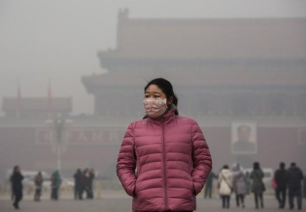 Mulher chinesa usa máscara para se proteger durante visita à praça Tiananmen em dia de alerta de poluição em Pequim, na China (Foto: Kevin Frayer/Getty Images)