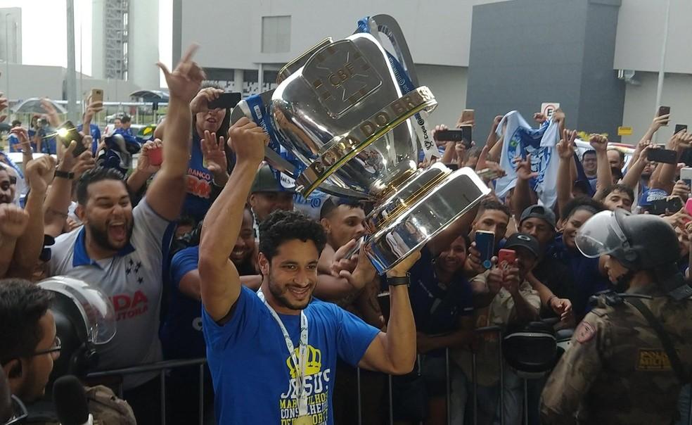 Léo ergueu o troféu na chegada ao aeroporto — Foto: Guilherme Macedo
