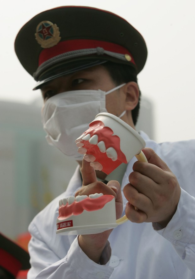 "XIAN, CHINA - SEPTEMBER 20: (CHINA OUT) A dentist shows a model of the human mouth during an event to mark the Love Teeth Day at a street on September 20, 2006 in Xian of Shaanxi Province, China. A massive campaign on ""Love Teeth Day"" (LTD) was initiated  (Foto: Getty Images)"