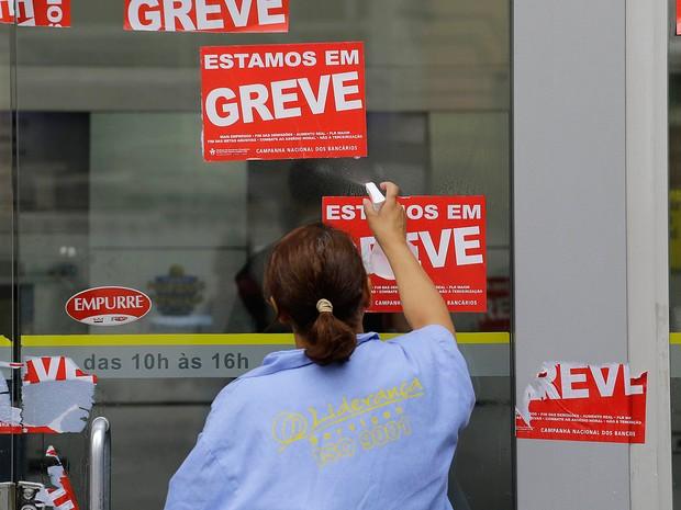 Funcionária limpa fachada de banco na região central de São Paulo nesta sexta-feira (7) após o fim do greve (Foto: Nelson Antoine/FRAMEPHOTO/Estadão Conteúdo)
