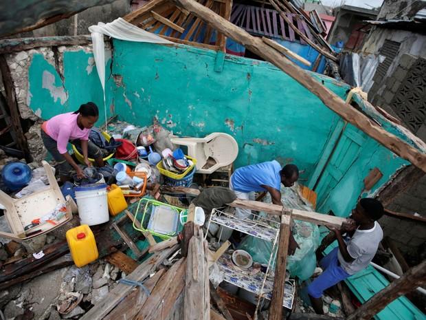 Moradores limpam casa destruída por passagem do furacão Matthew em Les Cayes, no Haiti, na quarta (5) (Foto: Reuters/Andres Martinez Casar)