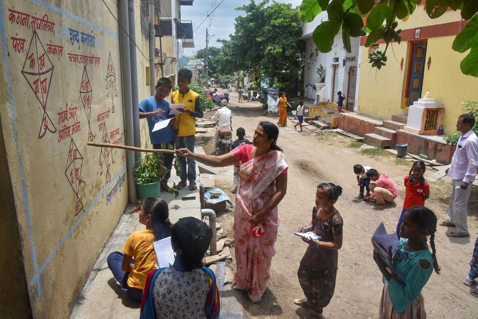 Professores de vilarejo rural da Índia estão escrevendo lições nas paredes para driblar o fechamento das escolas devido à pandemia do coronavírus. — Foto: AFP