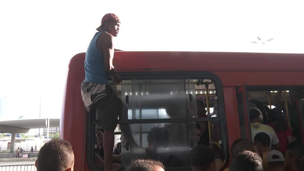 Passageiro entra pela janela do ônibus no TI Joana Bezerra, no Centro do Recife, na terça (24) — Foto: Reprodução/TV Globo