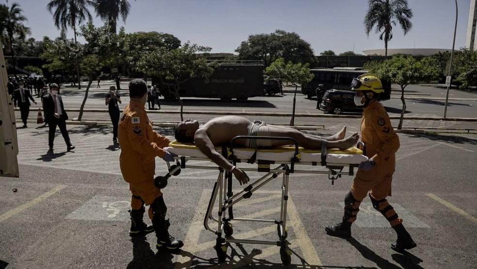 Indígena é socorrido por bombeiros após confronto em Brasília — Foto: Leo Otero