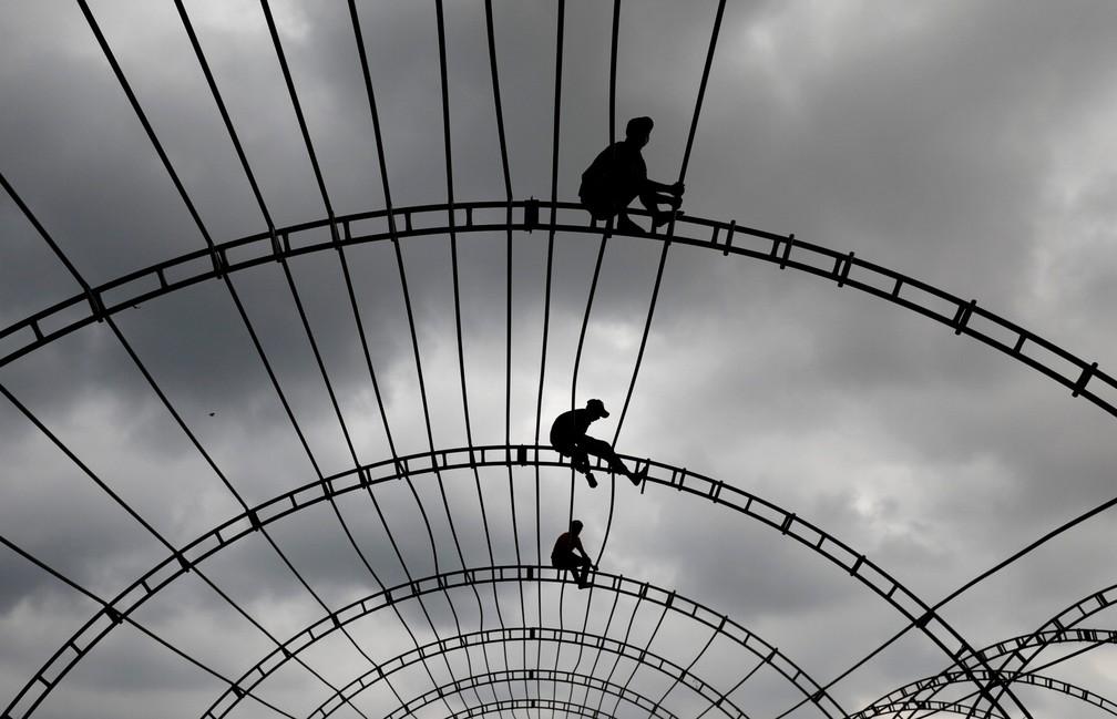 Homens trabalham na estrutura de uma tenda para um evento em Colombo, no Sri Lanka — Foto: Dinuka Liyanawatte/Reuters