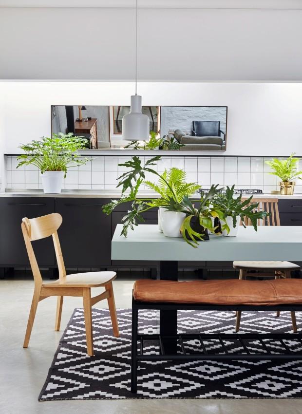 Acolhedor. No piso cimentício, o tapete aquece a área com mesa e banco de aço criados pelo designer Christo Vermeulen. Cadeiras nos estilos Bentwood e Ercol (Foto: Greg Cox / Bureaux.co.za)