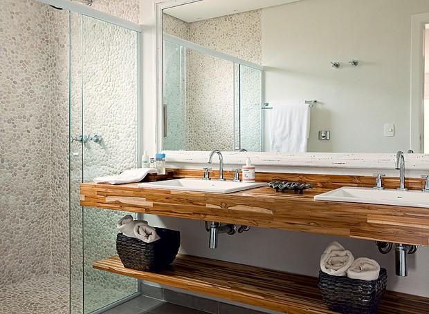Para levar a natureza para dentro do banheiro de 7 m², a arquiteta Ana Karina Abud projetou o boxe com revestimento de seixos telados na cor areia. As duas pias ficam sobre a bancada de madeira teca (Foto: Edu Castello)
