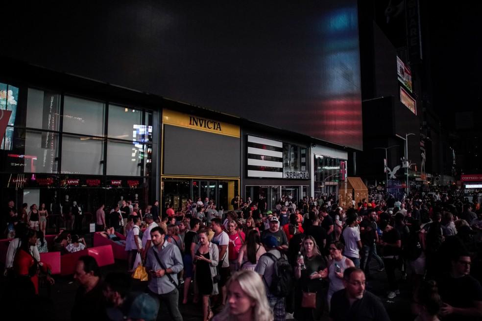 Pessoas caminham ao lado de prédio apagado depois de blecaute que atingiu pontos turísticos de Nova York neste sábado (13) — Foto: Jeenah Moon/Reuters