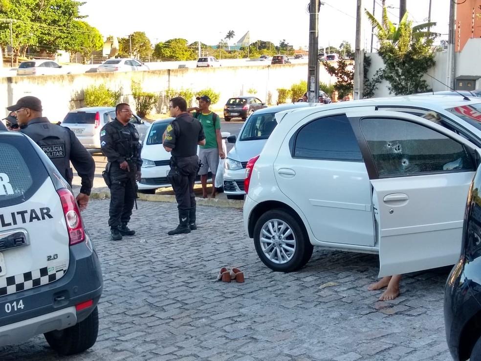 Marcas de tiros na porta de carro onde estava casal alvo de tiros na tarde desta sexta-feira (22) na Zona Sul de Natal. Uma das vítimas está sentada à porta. — Foto: Igor Jácome/G1