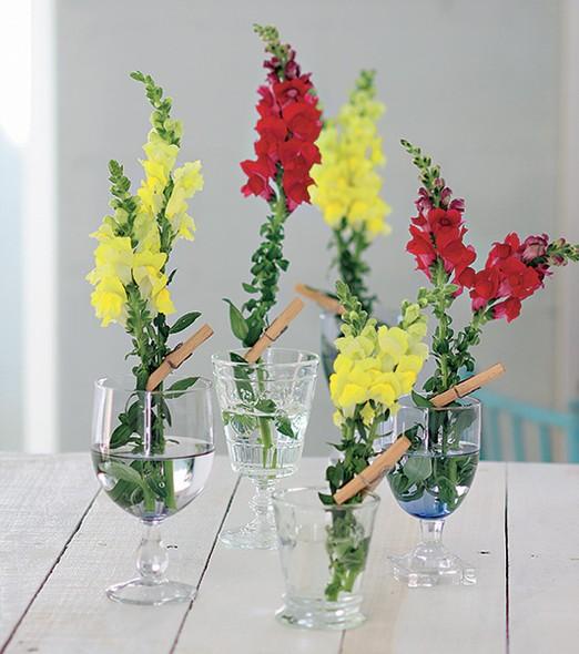 No lugar de um grande arranjo, experimente espalhar as flores em pequenos vasos. Taças e copos de alturas diversas viram solitários para uma composição colorida e delicada
