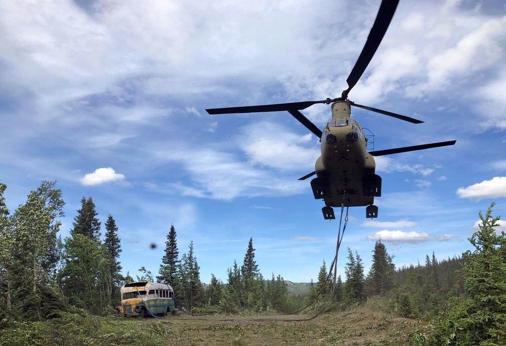 Helicóptero se aproxima de ônibus que ficou famoso no livro e no filme 'Na natureza selvagem' sobre o Parque Nacional de Denali, no Alasca — Foto: Seth Lacount/Guarda Nacional do Exército do Alasca/AFP