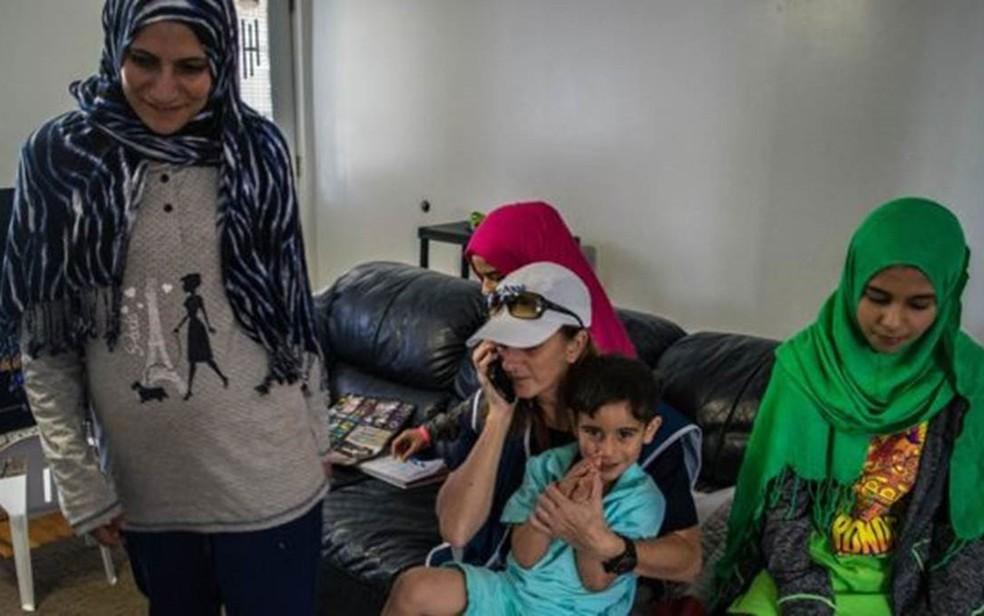 Rachel (ao telefone) conhece uma família de refugiados sírios  (Foto: Andreane Williams/Divulgação)