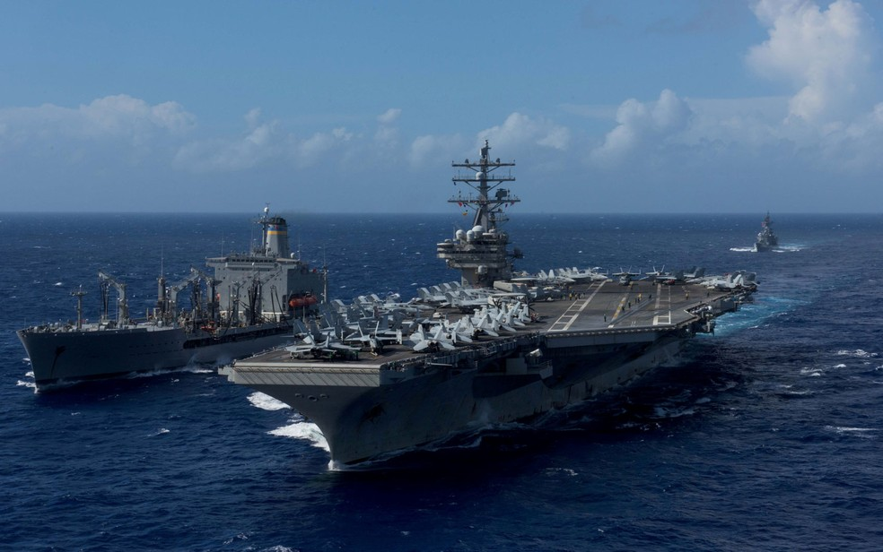 O USS Ronald Reagan (direita), que atualmente participa de exercícios militares na península coreana, é visto durante operação de reabastecimento no mar nas águas ao redor de Okinawa, em foto de 9 de outubro (Foto: U.S. Navy/Mass Communication Specialist 2nd Class Kenneth Abbate/via Reuters)