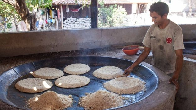 Assar os bijus é uma das primeiras etapas no processo tradicional de produção da tiquira (Foto: Dubes Sonego Junior/via BBC News Brasil)