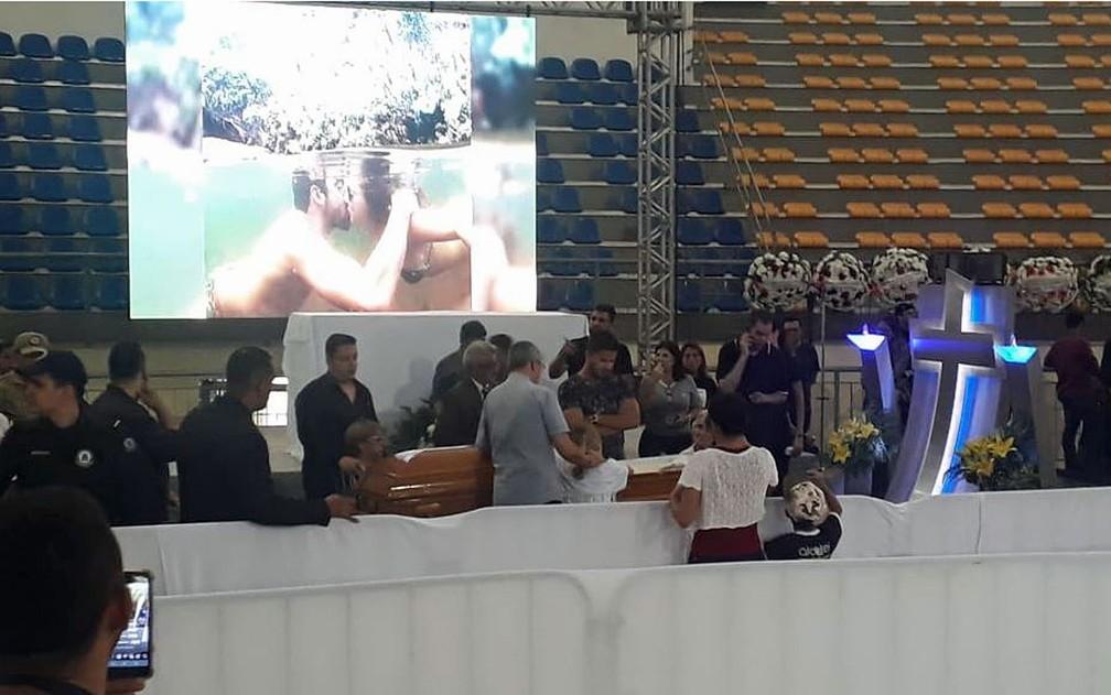 Namorada de Gabriel Diniz, Karoline Calheiros (centro, de camiseta branca junto ao caixão), agachada diante do caixão do cantor com familiares e fãs no velório, em ginásio de João Pessoa — Foto: André Resende/G1