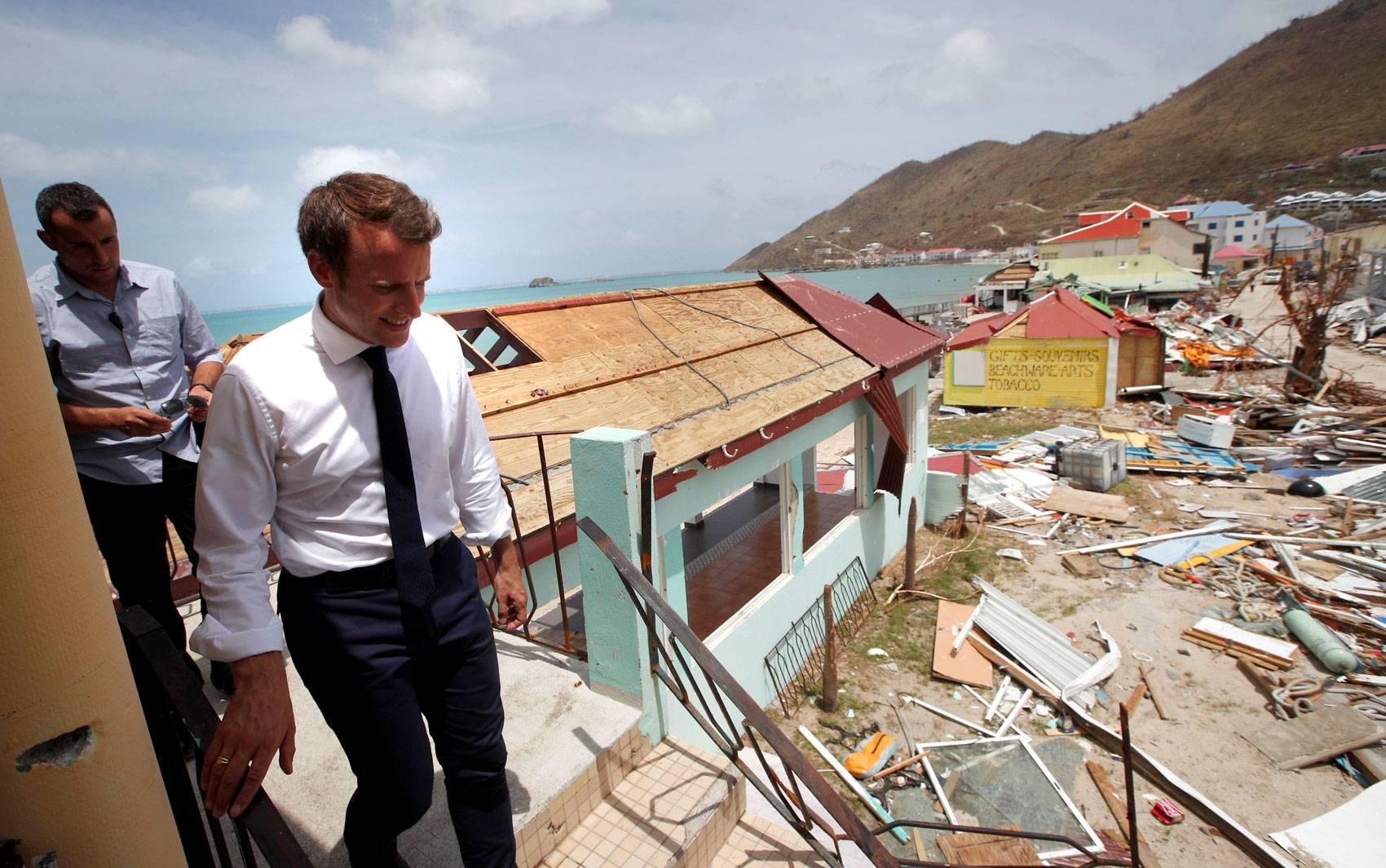 O presidente francês Emmanuel Macron passa por prédios destruídos pela passagem do furacão Irma na ilha francesa de St. Martin, no Caribe, durante visita na terça-feira (12)