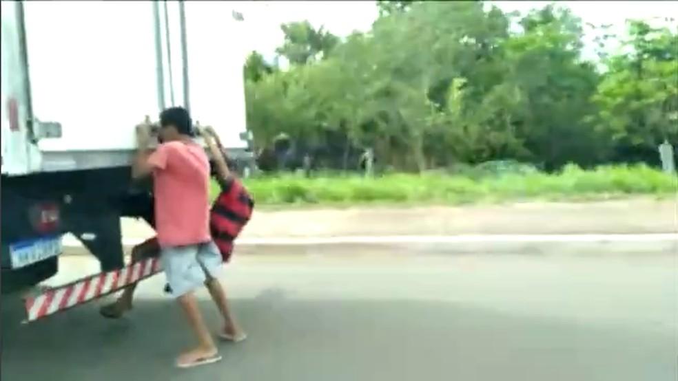 Adolescentes pegando rabeira em caminhão — Foto: Reprodução/TV Anhanguera