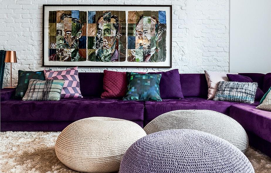 O sofá roxo com linhas retas compõe a sala de TV com os grandes pufes. Projeto do arquiteto Thiago Passos