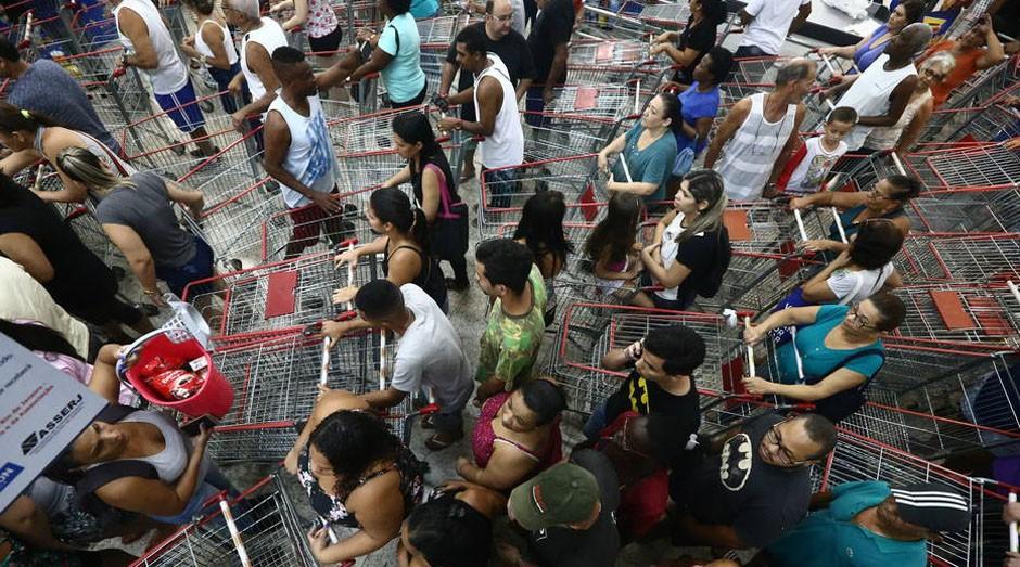 Consumidores fizeram fila nas portas dos supermercados da rede Guanabara desde a madrugada (Foto: Reprodução/Estadão Conteúdo)