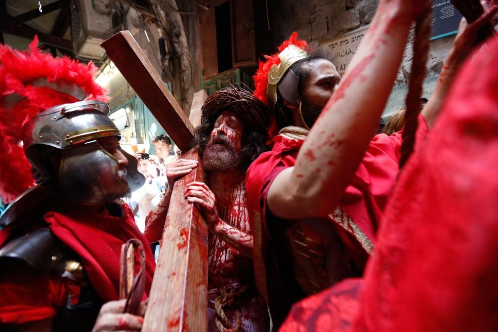 Ator vestido como Jesus Cristo carrega uma cruz em caminhada pela Via Dolorosa, na direção à Igreja do Santo Sepulcro, na Cidade Velha de Jerusalém — Foto: Ariel Schalit/AP