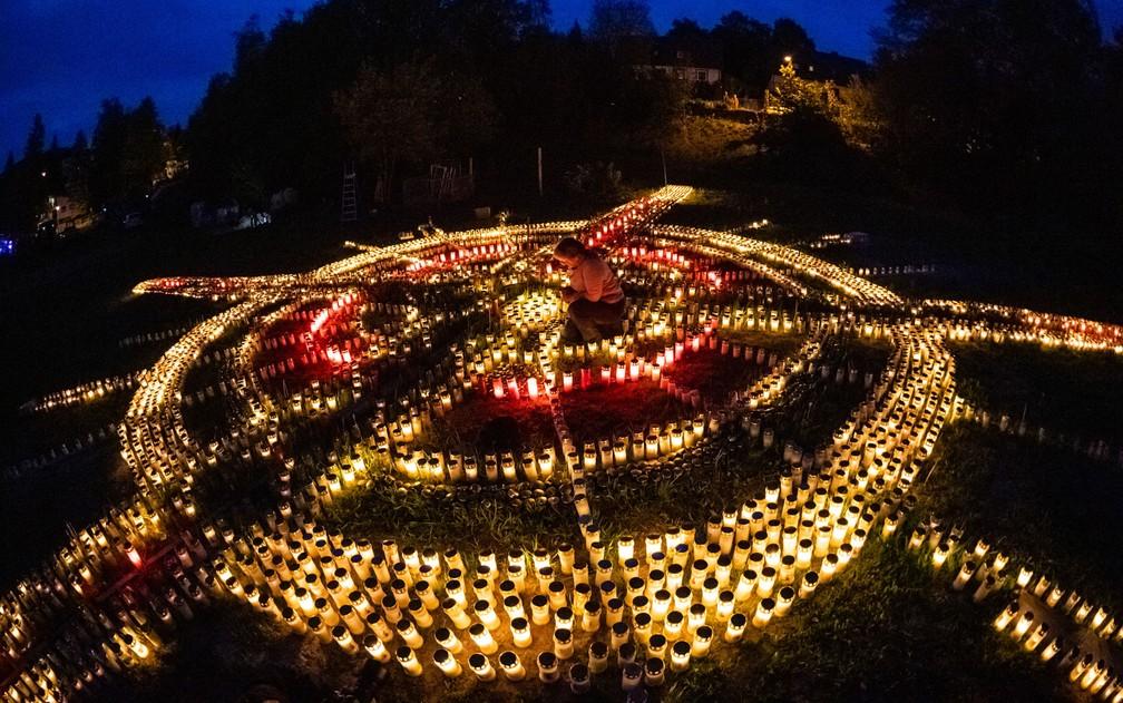 Gertrud Schop acende velas na forma de uma cruz, dedicadas às vítimas de Covid-19 na Alemanha, em Zella-Mehlis  — Foto: Jens Schlueter/AFP