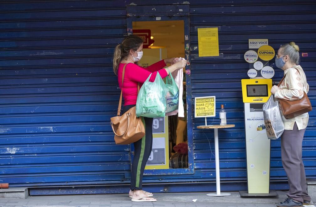 1º de junho: cliente checa mercadoria em loja que ficou aberta para entregar encomendas compras feitas online em São Paulo. — Foto: André Penner/AP