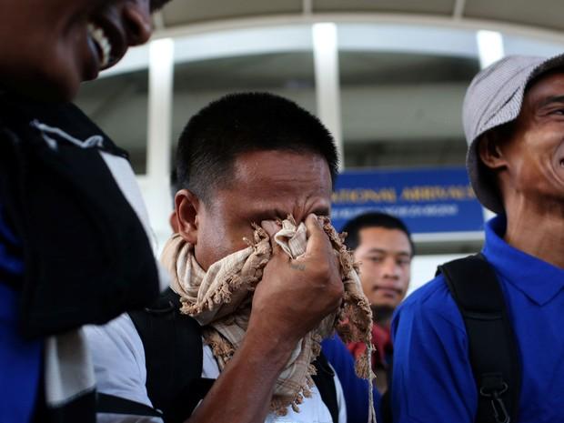 Alguns dos homens mantidos reféns por piratas somalis durante quase cinco anos se emocionam ao chegar ao aeroporto internacional de Nairobi, no Quênia, no domingo (23) (Foto: Reuters/Siegfried Modola)