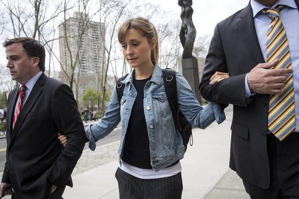A atriz Allison Mack deixando a prisão na qual estava detida em Nova York na companhia de seus advogados (Foto: Getty Images)