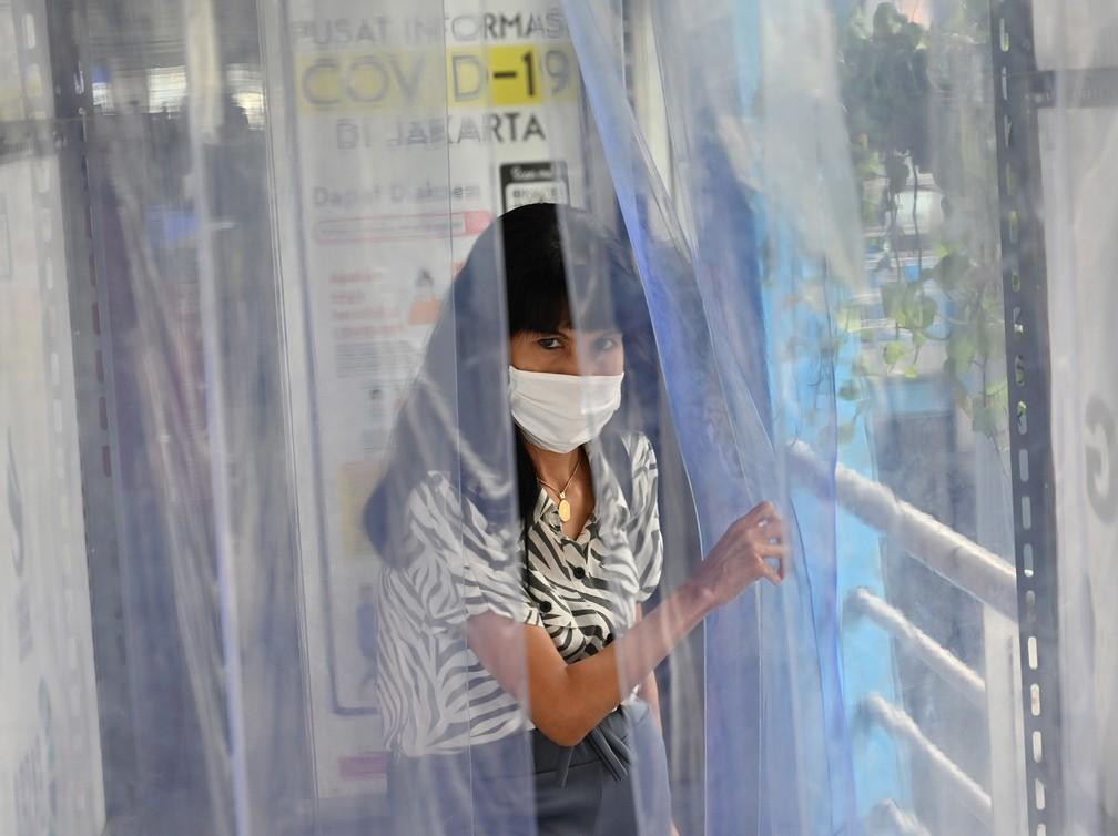 6 de abril - Uma mulher atravessa uma câmara de desinfecção na estação de ônibus Harmony, em Jacarta, Indonésia — Foto: Adek Berry/AFP