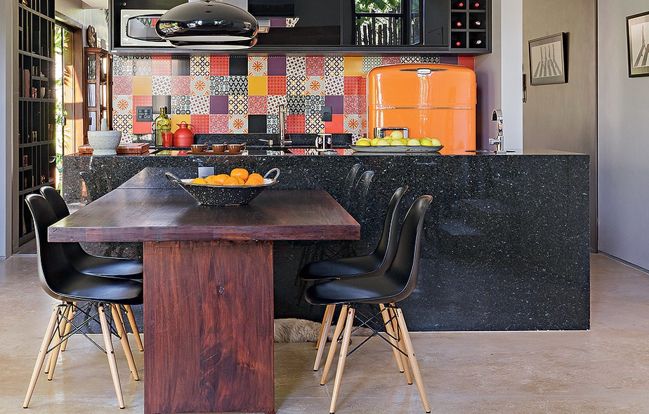 Na cozinha aberta para a sala de jantar o destaque é a geladeira antiga, herdada da avó da moradora, com pintura laranja. A cor foi definida a partir do mosaico de azulejos que cobre a parede acima da pia. Projeto do arquiteto Ney Lima