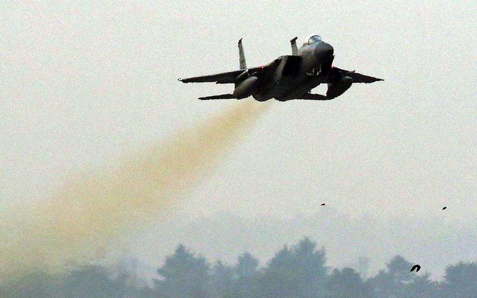 Um caça F-15 da Força Aérea dos Estados Unidos voa sobre uma base aérea sul-coreana em Gwangju (Foto: YONHAP / via AFP Photo)