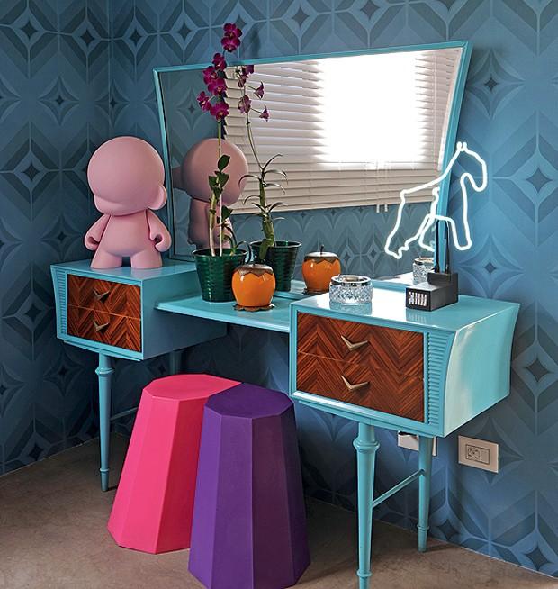 A penteadeira retrô ganhou um ar inusitado com a tinta azul. A toy art e o neon deixam o móvel moderno e divertido.  (Foto: Marcelo Magnani/Casa e Jardim)
