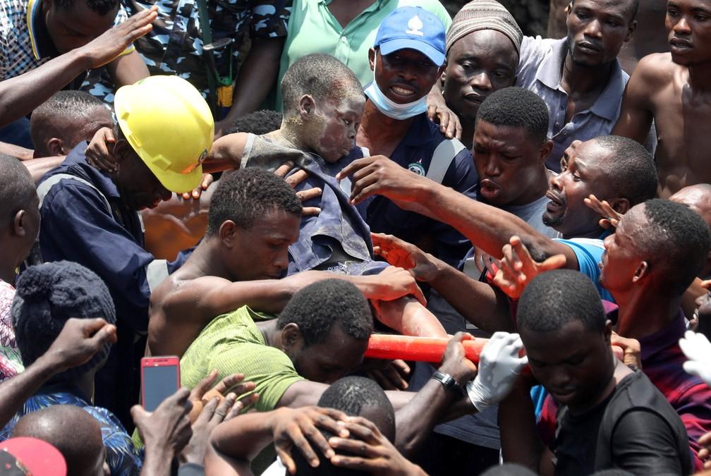 Homens carregam criança resgatada dos escombros de escola que desabou em Lagos, na Nigéria — Foto: Temilade Adelaja/Reuters