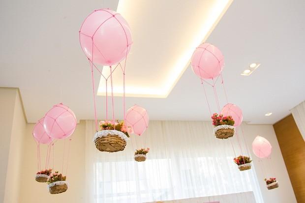 A inspiração para o tema veio de uma foto em que balões voavam com uma cestinha de flores. Por que não posicioná-los em frente à mesa e criar um clima mais encantador? A Manginelli Balões usou ganchos colados com fita banana para não causar dano ao teto do salão alugado  (Foto: Danilo Giunchetti)