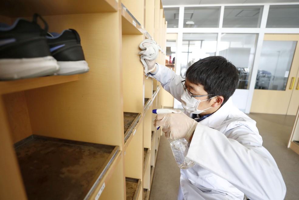 Homem usa equipamento de proteção para desinfetar uma escola primária em Kitahiroshima, no Japão, nesta quinta-feira (27). — Foto: Kyodo via Reuters