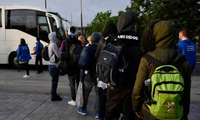 Em Paris, migrantes irregulares são retirados do campo de Millenaire para embarcar em ônibus que os levará para abrigos temporários