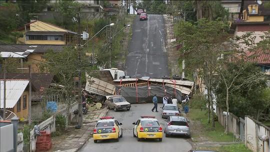 Caminhão destrói parte de casa depois de tombar em rua de Campo Largo