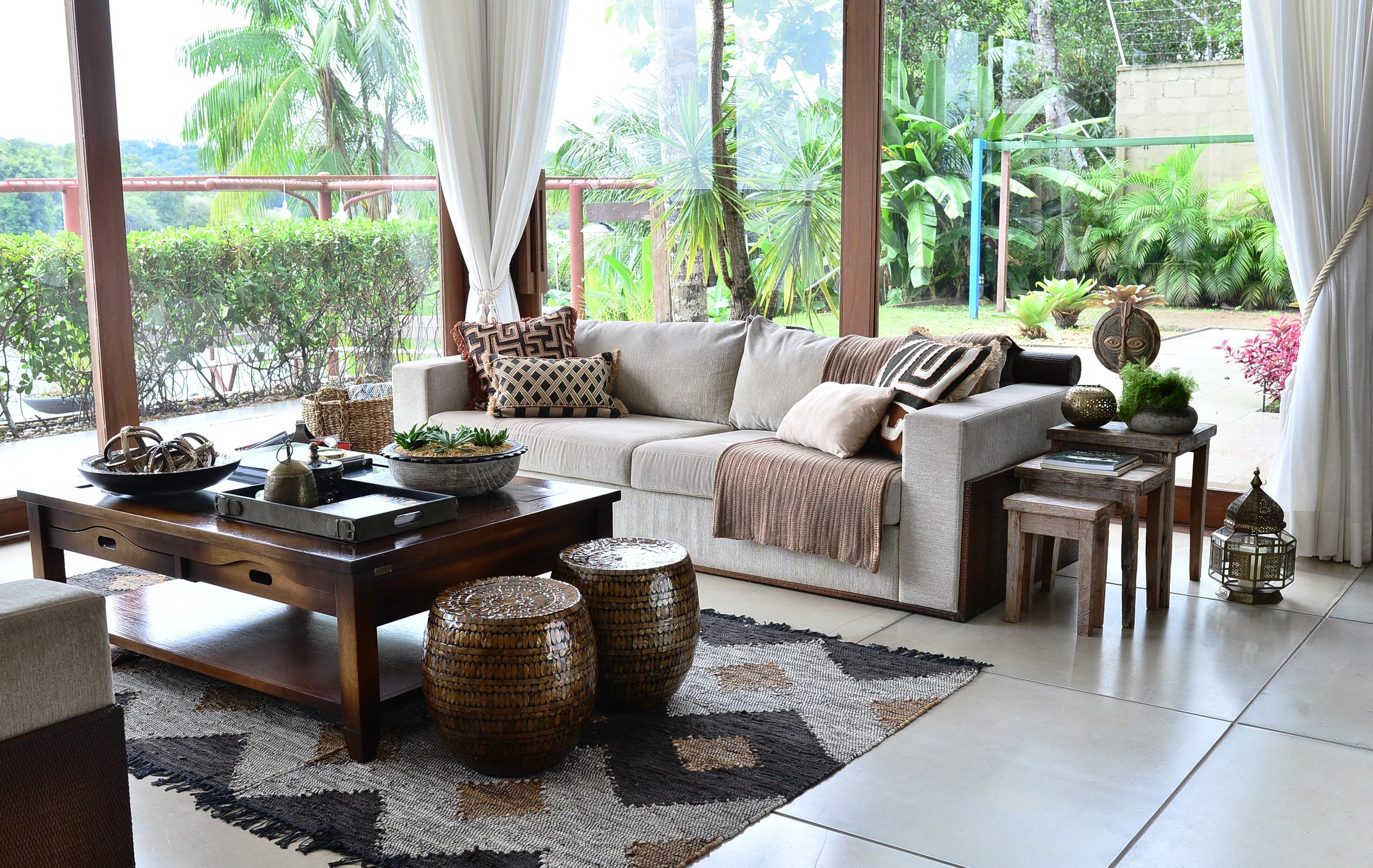 O visual do interior e do exterior integra-se através de panos de vidro na sala de estar (Foto: Divulgação)