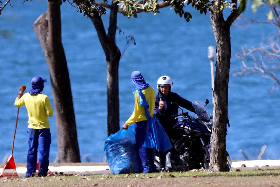 Sem máscara, o presidente Jair Bolsonaro conversa com funcionários do Palácio da Alvorada, em Brasília, após tirar o capacete durante passeio de moto dentro da área do palácio. — Foto: Foto: Adriano Machado/Reuters