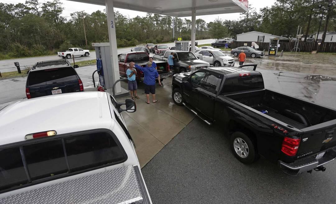 Após o furacão, filas de carros se formam para abastecer em um posto de gasolina com gerador