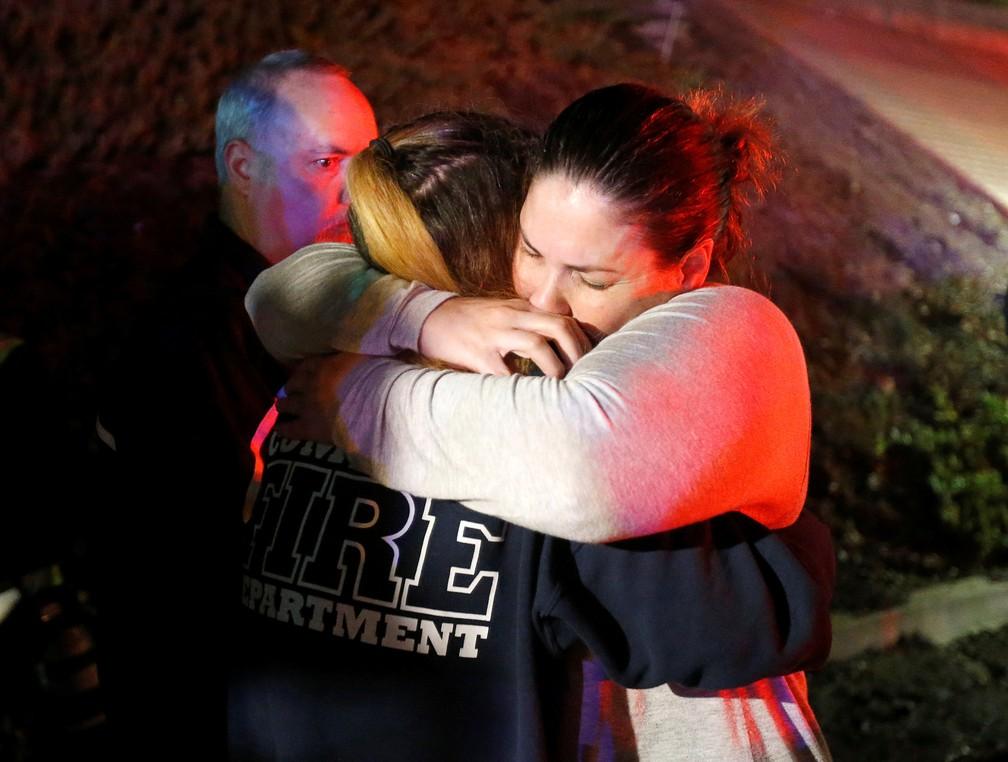 Jovens se abraçam após tiroteio em casa noturna de Thousand Oaks, na Califórnia — Foto: Ringo Chiu/Reuters