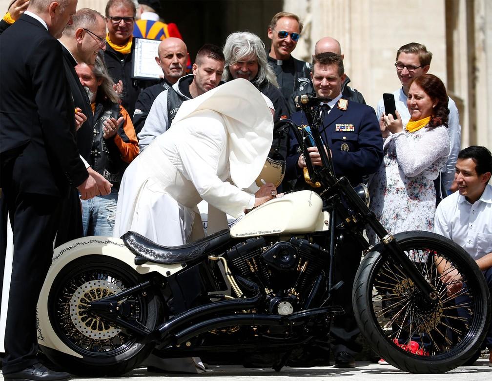 29 de maio - O Papa Francisco autografa uma motocicleta do grupo cristão de motoqueiros 'Jesus Biker' no momento em que o vento sopra sua roupa durante audiência-geral semanal no Vaticano — Foto: Yara Nardi/Reuters