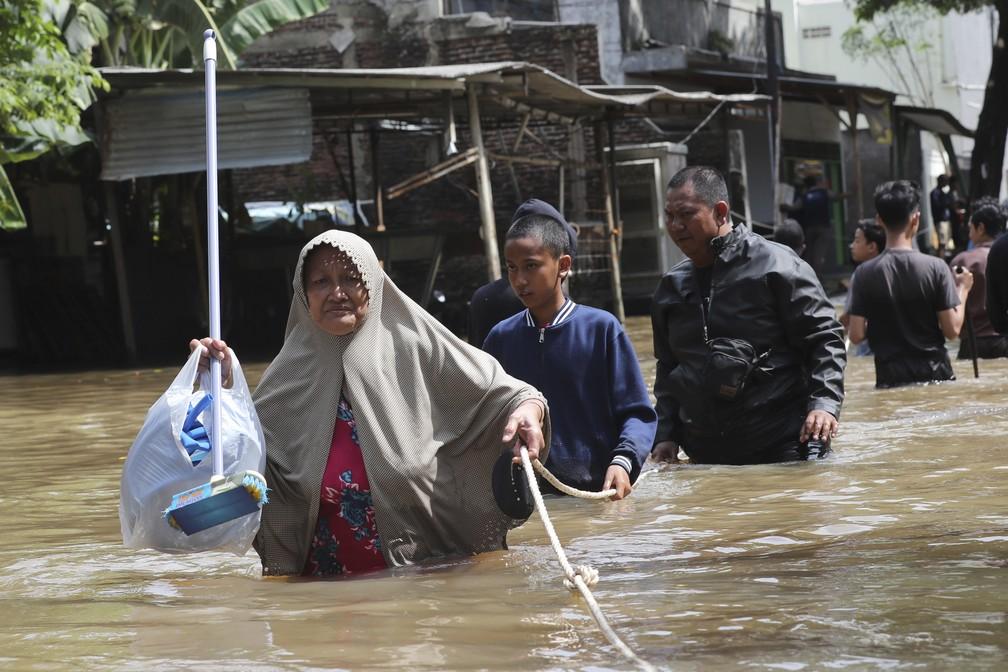 Moradores em um bairro inundado em Tanggerang, nos arredores de Jacarta, na Indonésia — Foto: Tatan Syuflana/AP